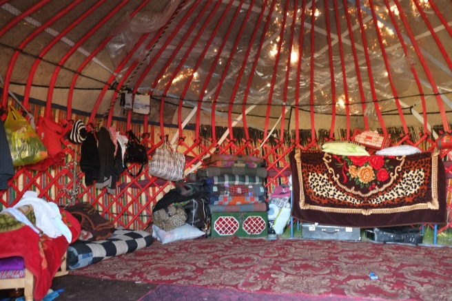 The inside of a sleeping yurt: mattresses, blankets and pillows are neatly folded and stored along the felt walls during the day. There are always enough blankets to host a few more guests.